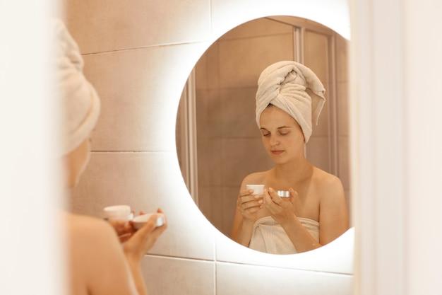 Portret van een jonge volwassen vrouw die in de badkamer voor de spiegel staat met crème in handen, thuis schoonheidsprocedures doet na het douchen, gewikkeld in een witte handdoek.