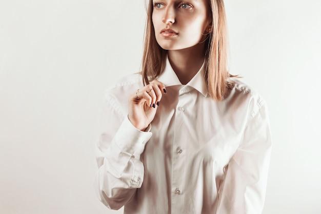Portret van een jonge volwassen vrouw met kraag van wit overhemd met haar hand,