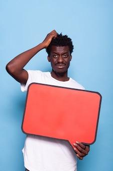 Portret van een jonge volwassene die een leeg bord vasthoudt voor communicatie