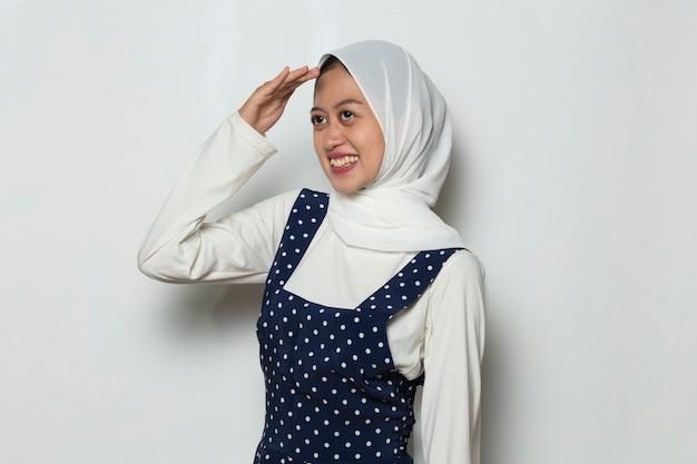 Portret van een jonge, vrij nieuwsgierige moslimvrouw die als een verrekijker door haar vingers gluurt