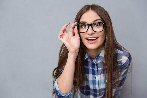 Portret van een jonge, vrij nieuwsgierige vrolijke vrouw met een bril
