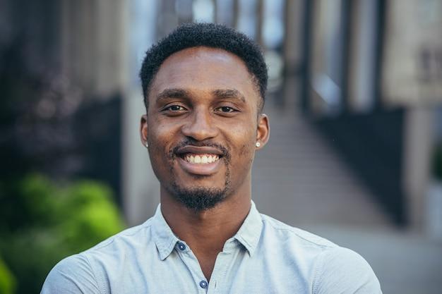 Portret van een jonge, vrolijke afro-amerikaanse man die naar de camera kijkt, glimlacht en zich verheugt