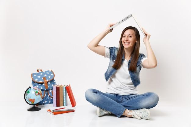 Portret van een jonge, vrolijke, mooie vrouw die een laptop pc-computer boven het hoofd houdt als een dak in de buurt van een schoolboek met een wereldrugzak