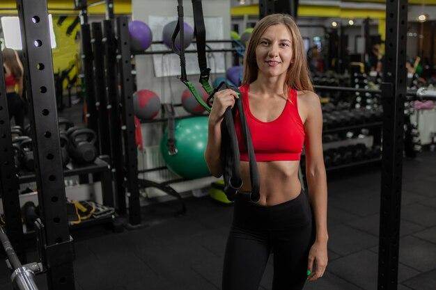 Portret van een jonge vrolijke slanke vrouw in sportkleding in een moderne sportschool
