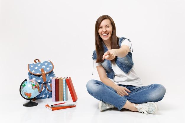 Portret van een jonge, vrolijke studente die met de wijsvinger op de camera wijst en in de buurt van de wereldbol, rugzak, geïsoleerde schoolboeken zit