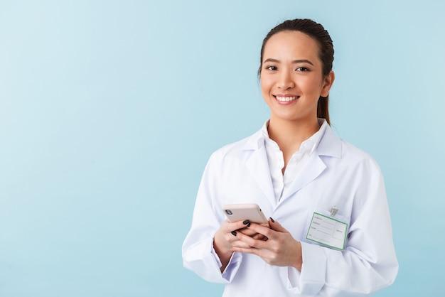 Portret van een jonge vrouw arts poseren geïsoleerd over blauwe muur met behulp van mobiele telefoon.