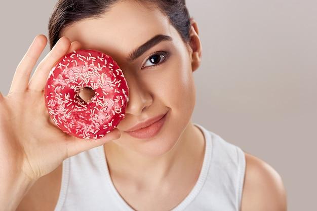 Portret van een jonge vrouw bedekt haar gezicht met roze donut op beige achtergrond