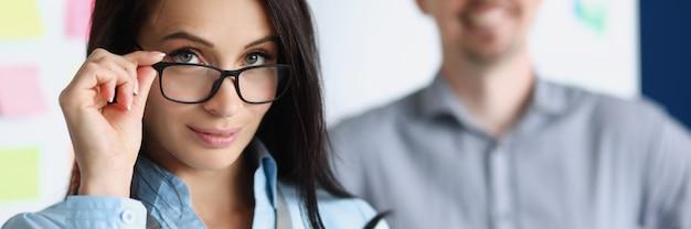 Portret van een jonge vrouw bedrijfsadviseur tegen de achtergrond van een mannelijke collega op kantoor