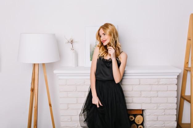 Portret van een jonge vrouw, blond meisje in lichte kamer met mooi, modern wit interieur, staande naast nep open haard, op zoek naar kant. stijlvolle zwarte jurk dragen.