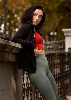 Portret van een jonge vrouw buitenshuis poseren