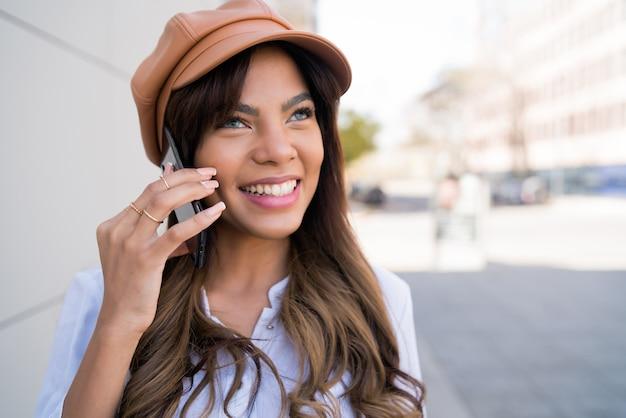 Portret van een jonge vrouw die aan de telefoon praat terwijl ze buiten op straat staat. stedelijk en communicatieconcept.