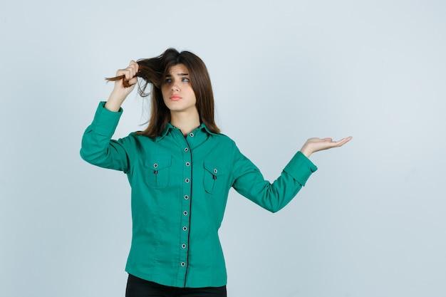 Portret van een jonge vrouw die aan haar haren trekt, de palm opzij spreidt in een groen shirt en teleurgesteld vooraanzicht kijkt