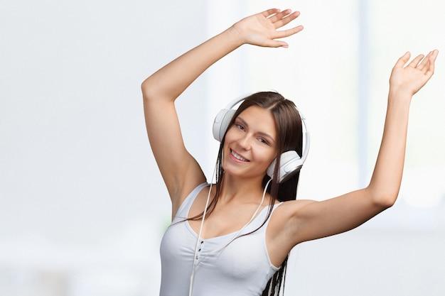 Portret van een jonge vrouw die aan muziek met hoofdtelefoons luistert