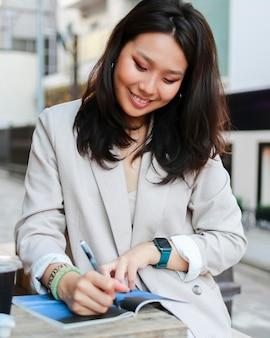 Portret van een jonge vrouw die aantekeningen maakt