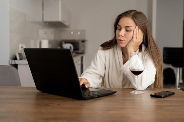 Portret van een jonge vrouw die achter laptop zit en geeuw. mooi meisje gekleed in een witte badjas