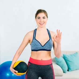 Portret van een jonge vrouw die bal in de hand tonen ok teken
