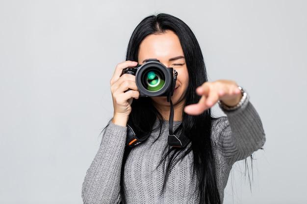 Portret van een jonge vrouw die beelden op de camera neemt, dat op grijze muur wordt geïsoleerd