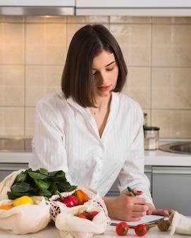 Portret van een jonge vrouw die boodschappenlijst controleert
