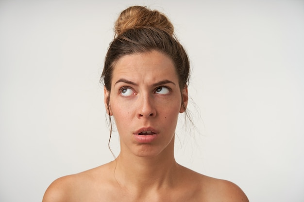Portret van een jonge vrouw die broodje kapsel en geen make-up draagt, naar boven kijkend met verveeld gezicht, staande op wit