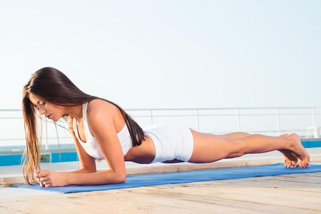 Portret van een jonge vrouw die buiten op yogamat uitwerkt