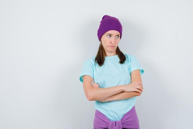 Portret van een jonge vrouw die de armen gevouwen houdt, wegkijkt in t-shirt, muts en er somber uit ziet