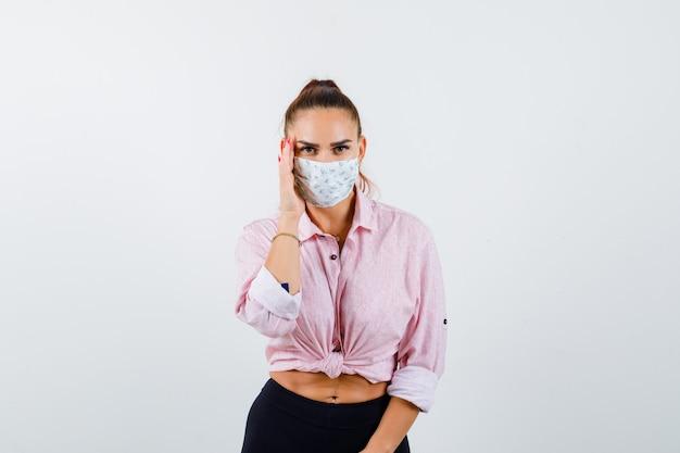 Portret van een jonge vrouw die de hand aan de zijkant van het gezicht in shirt, broek, masker houdt en nieuwsgierig vooraanzicht kijkt