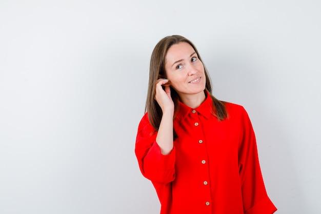 Portret van een jonge vrouw die de hand in de buurt van het oor houdt in een rode blouse en er nieuwsgierig uitziet aan de voorkant