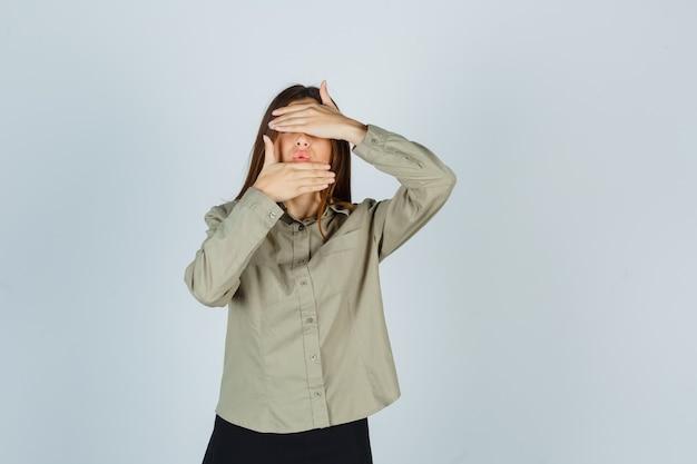 Portret van een jonge vrouw die de hand op de ogen en kin houdt, lippen pruilt in shirt, rok en bang vooraanzicht kijkt