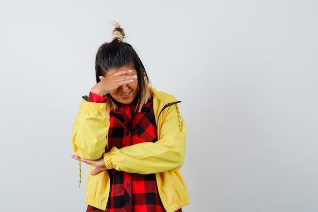 Portret van een jonge vrouw die de hand op het voorhoofd houdt, naar beneden kijkt in een geruit hemd, een jas en een vrolijk vooraanzicht kijkt
