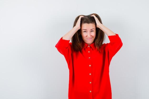 Portret van een jonge vrouw die de handen op het hoofd houdt in een rode blouse en er een verontrust vooraanzicht uitziet