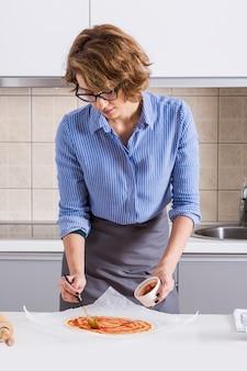 Portret van een jonge vrouw die de saus op pizzabrood uitspreidt over het perkamentdocument