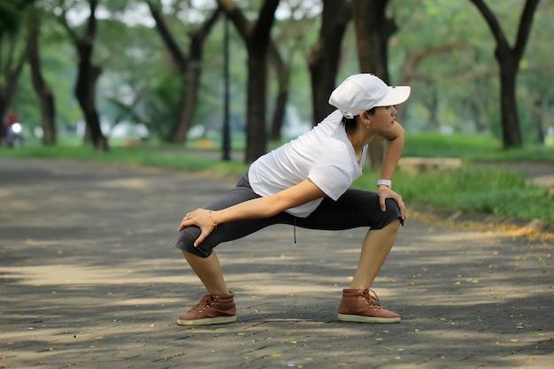 Portret van een jonge vrouw die de spieren uitrekken om op te warmen alvorens te lopen