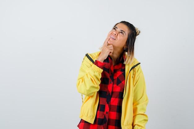 Portret van een jonge vrouw die de vinger op de kin houdt, omhoog kijkt in een geruit hemd, een jas en een hoopvol vooraanzicht kijkt
