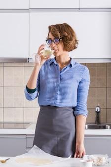 Portret van een jonge vrouw die de wijn drinkt terwijl het voorbereiden van de pizza