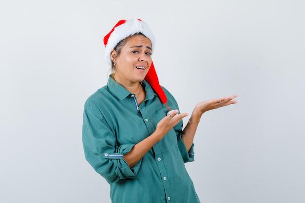 Portret van een jonge vrouw die doet alsof ze iets in shirt, kerstmuts laat zien en er verbaasd uitziet