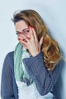 Portret van een jonge vrouw die door haar vingers naar de camera gluurt