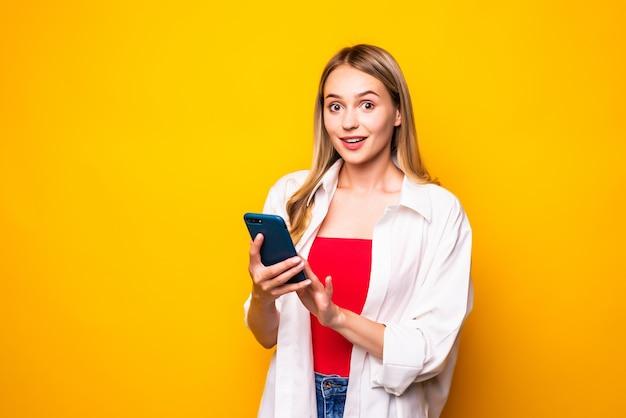 Portret van een jonge vrouw die door mobiele telefoon babbelt die over gele muurmuur wordt geïsoleerd.