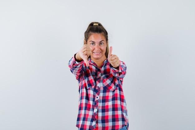 Portret van een jonge vrouw die duimen op en neer in casual overhemd toont en heel vooraanzicht kijkt