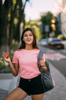 Portret van een jonge vrouw die een appel vasthoudt tegen een straat