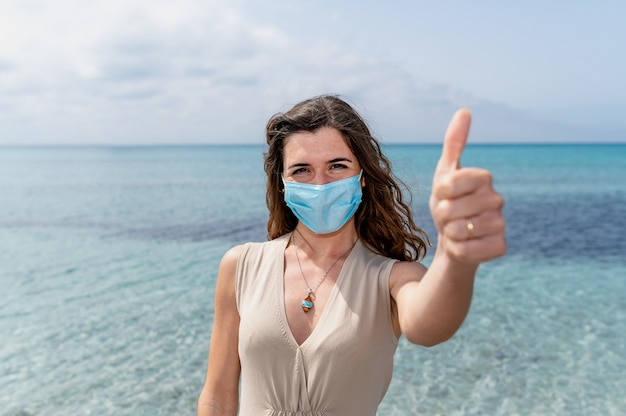 Portret van een jonge vrouw die een beschermend gezichtsmasker draagt dat duim toont. mooie achtergrond met blauw helder water