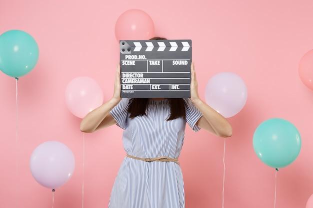Portret van een jonge vrouw die een blauwe jurk draagt die haar gezicht bedekt met klassieke zwarte film die filmklapper maakt op een roze achtergrond met kleurrijke luchtballonnen. verjaardagsfeestje, oprechte emoties van mensen.