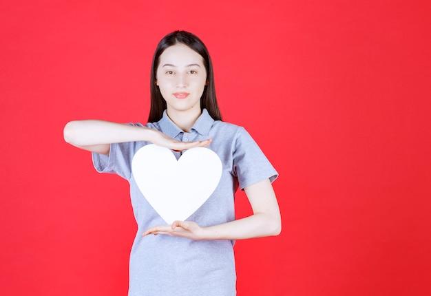 Portret van een jonge vrouw die een bord in de vorm van een hart vasthoudt en naar de voorkant kijkt