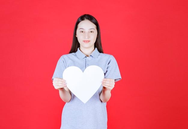 Portret van een jonge vrouw die een bord in de vorm van een hart vasthoudt