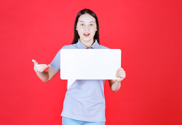 Portret van een jonge vrouw die een bord vasthoudt en de hand erop wijst