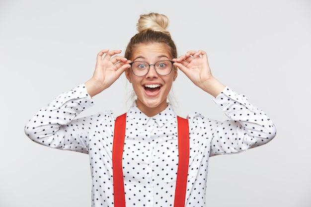 Portret van een jonge vrouw die een bril houdt en naar de voorkant kijkt
