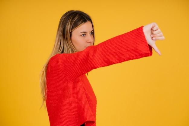 Portret van een jonge vrouw die een duim naar iemand laat zien terwijl ze tegen een geïsoleerde achtergrond staat.