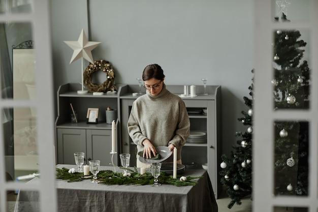 Portret van een jonge vrouw die een eettafel opzet in de eetkamer die is ingericht voor kerstmis met sparrenzemelen