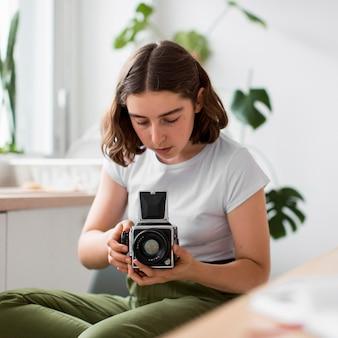 Portret van een jonge vrouw die een foto met camera neemt