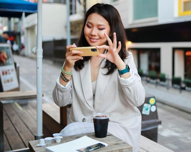 Portret van een jonge vrouw die een foto van een snack neemt