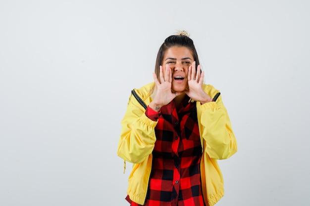 Portret van een jonge vrouw die een geheim vertelt, de handen in de buurt van de mond houdt in een geruit hemd, een jas en een vrolijk vooraanzicht kijkt